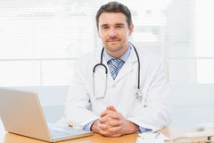 Male doctor with laptop at desk in medical office Royalty Free Stock Image