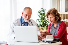 Doctor with laptop talking to a senior woman in office. Male doctor with laptop talking to a senior women in his office stock photography