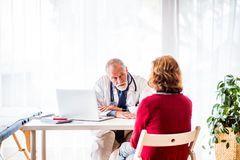 Doctor with laptop talking to a senior woman in office. Male doctor with laptop talking to a senior women in his office royalty free stock photography