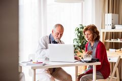 Doctor with laptop talking to a senior woman in office. Male doctor with laptop talking to a senior women in his office stock photo