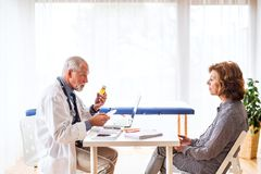 Doctor with laptop talking to a senior woman in office. Male doctor with laptop talking to a senior women in his office royalty free stock photos