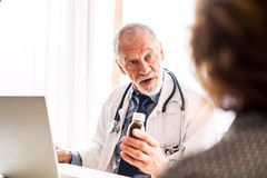 Doctor with laptop talking to a senior woman in office. Male doctor with laptop talking to a senior women in his office stock image
