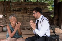 Male Doctor listening heart beat and breathing of Elderly Woman Royalty Free Stock Images