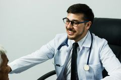 Male Doctor listening heart beat and breathing of Elderly Woman Stock Photo