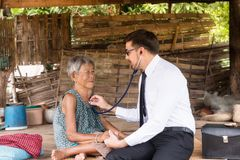 Male Doctor listening heart beat and breathing of Elderly Woman royalty free stock photo