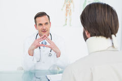 Male doctor listening to patient with concentration at desk Stock Photos
