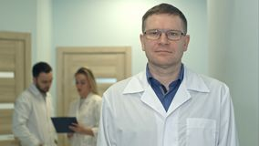 Male doctor looking at camera while medical staff working on the background. Professional shot in 4K resolution. 097. You can use it e.g. in your commercial Royalty Free Stock Photos