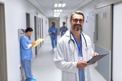 Male doctor looking at camera while writing on clipboard in corridor at hospital. royalty free stock images