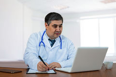 A male doctor is looking at the computer. Doctor in the medical center. Sits by the table Stock Image