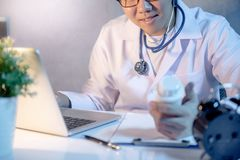 Male doctor looking at pill bottle working in hospital. Male Asian doctor looking at pill bottle on his hand working with laptop computer and medicine paperwork Royalty Free Stock Photography
