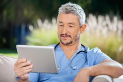 Male Doctor Looking At Tablet PC Stock Images
