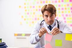 The male doctor with many conflicting prioritites stock photography