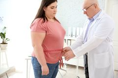 Male doctor measuring waist of overweight woman. Male doctor measuring waist of overweight women in clinic stock photos