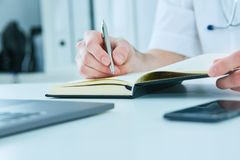 Male doctor or medical student holding ballpoint pen and writing on notepad. Therapist fills the patient admission. Close up male doctor`s hand holding ballpoint stock image