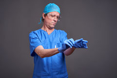 A male doctor. A middle aged male doctor in blue scrubs taking his gloves on and getting ready Stock Images
