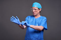 A male doctor. A middle aged male doctor in blue scrubs taking his gloves on and getting ready Royalty Free Stock Photos