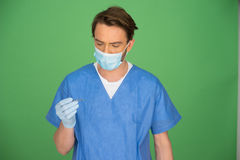 Male doctor or nurse looking at his gloved hand Stock Photography