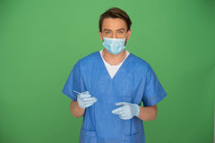 Male doctor or nurse looking at his gloved hand Royalty Free Stock Photography