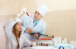 Male doctor and nurse in medical laboratory. Male doctor and nurse with test tubes makes blood test in medical laboratory Stock Photography