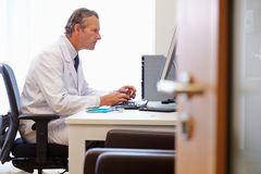Male Doctor In Office Working At Computer Stock Image