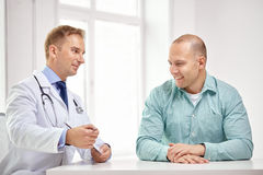 Male doctor and patient with clipboard at hospital. Medicine, health care, people and prostate cancer concept - happy male doctor with clipboard and patient royalty free stock photos