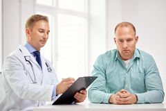 Male doctor and patient with clipboard at hospital Royalty Free Stock Image