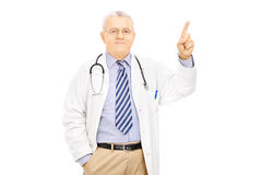 Male doctor pointing with finger upwards Royalty Free Stock Photo