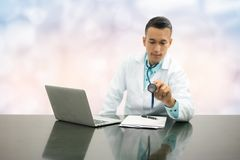 Male Doctor Working on Office Desk in Hospital Royalty Free Stock Photography