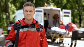 Male doctor posing for camera, ambulance crew transporting patient to clinic stock photo
