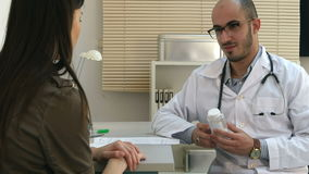 Male doctor prescribing pills to female patient and explaining side effects stock video footage
