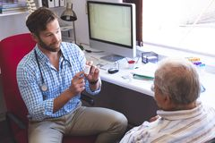 Free Male Doctor Prescribing Pills To His Senior Male Patient In Clinic Stock Photo - 143808760