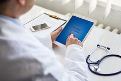 Male doctor presses on digital tablet royalty free stock image