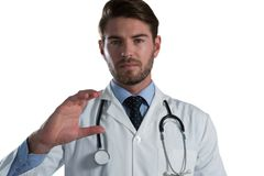 Male doctor pretending to hold an invisible object. Against white background Royalty Free Stock Photography