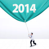Male doctor pulls a banner of new year 2014 Royalty Free Stock Photo