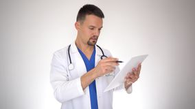 Male doctor reading medical document, writing prescription, portrait stock video