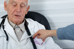Male Doctor receiving money from patient royalty free stock images