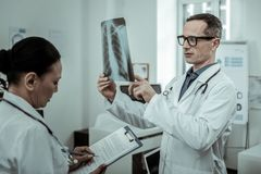 Male doctor reviewing rib cage with photo. Fracture or crack. Male doctor reviewing rib cage with photo while his assistant writing down main evidences stock photos