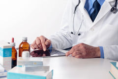 Male doctor`s hands with stethoscope at desk using digital table Royalty Free Stock Photo