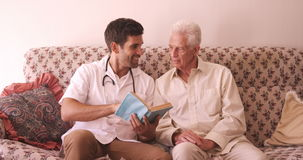 Male doctor and senior man reading a book. At hospital stock footage