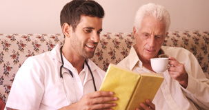 Male doctor and senior man reading a book stock video