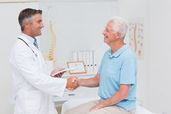 Male doctor and senior patient shaking hands Royalty Free Stock Images