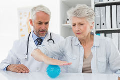 Male doctor with senior patient using stress buster ball. At the medical office Stock Photo