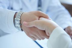 Male doctor shaking hands with patient. Partnership, trust and medical ethics concept. Handshake with satisfied client royalty free stock image