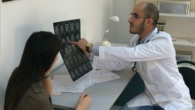 Male doctor showing brain computed tomography to female patient and filling in form stock images