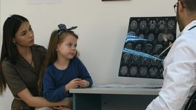 Male doctor showing brain xray results to happy and relieved woman with little girl royalty free stock photo