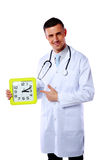 Male doctor showing on clock Stock Photos