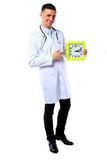 Male doctor showing on clock Stock Images