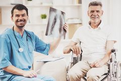 Male Doctor Showing Diagnosis of X-ray Image. Male Doctor Showing Diagnosis of X-ray Image to Older Patient Sitting at Wheelchair. Old Man in Hospital. Concept royalty free stock photography