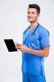 Male doctor showing finger on tablet computer screen. Portrait of a smiling male doctor showing finger on tablet computer screen isolated on a white background Royalty Free Stock Photos