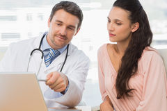 Male doctor showing something on laptop to patient Stock Images
